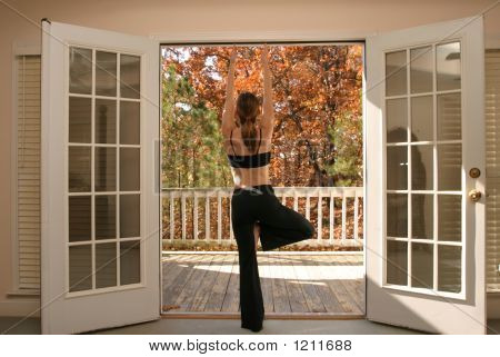 Woman Doing Yoga Looking Over Balcony