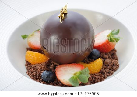 Chocolate ball dessert with ice cream inside serve on an assorted fruits