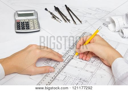 Architect working on blueprint. Architects workplace - architectural project, blueprints, ruler, calculator and divider compass. Construction concept. Engineering tools.