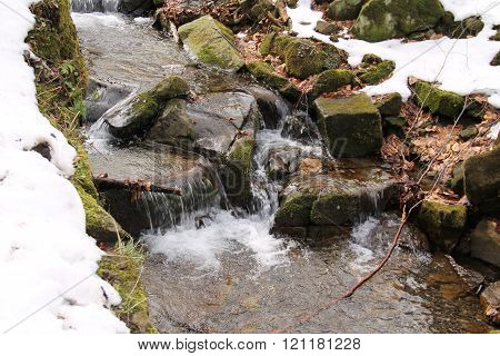 wild mountain brook in Beskydy mountains with remnants of snow on its banks