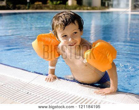 little cute real boy in swimming pool close up smiling