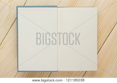 Open book with blank pages on textured wood background. Copy space