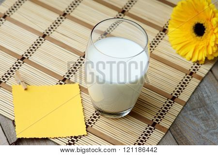 Glass of milk,gerber and yellow greeting card