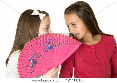 Two Beautiful Girls Talking Behind Oriental Fan Whisper Playing