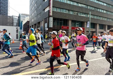 TOKYO, JAPAN - FEBRUARY 28 2016: Marathon in Tokyo Japan downtown. People running in the downtown of the Capital of Japan