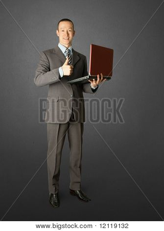 Full Length Portrait Of Businessman With Laptop