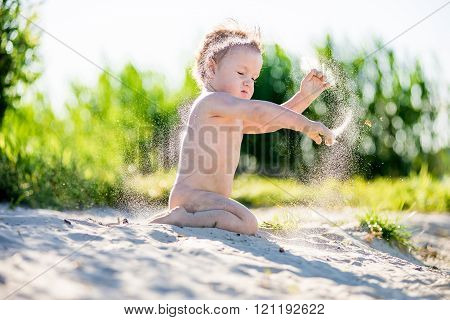 Little chubby toddler boy playing in the sandbox,  summer in Sunny weather. Throws sand