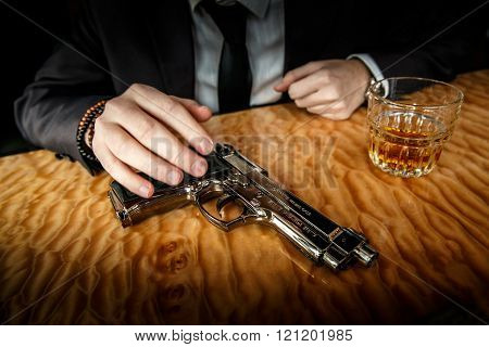 The gun with glass and cognac on the marble table