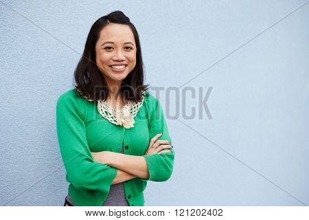 Waist up portrait of smiling Asian woman against grey wall