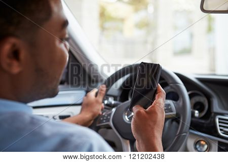 In car view of young male African American holding his phone