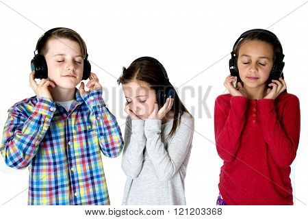Three Preteens Listening To Music With Headphones Eyes Closed Peaceful