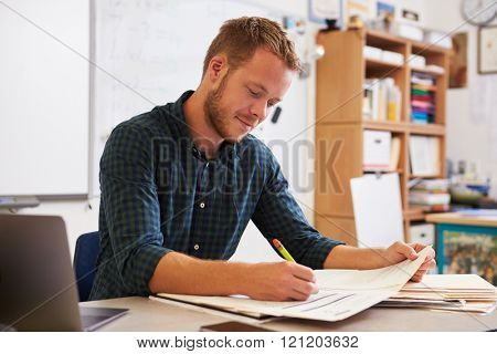 Young bearded male teacher at desk marking studentsâ?? work