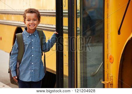 Elementary school boy getting onto a yellow school bus