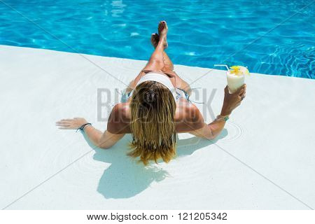 WOman at the swimming pool with a pina colada cocktail in her hand