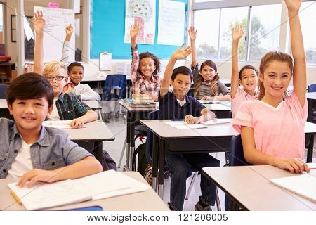 Elementary school kids in a classroom raising their hands