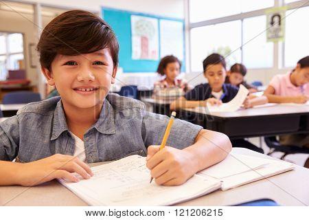 Asian schoolboy in elementary school class looking to camera