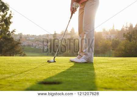 Close Up Of Male Golfer Lining Up Putt On Green