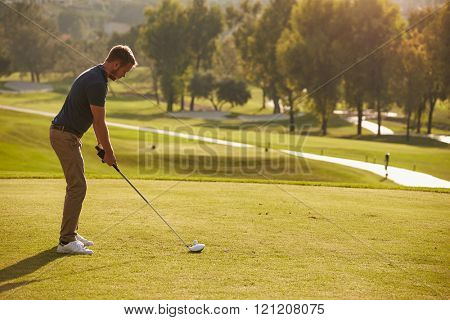 Male Golfer Lining Up Tee Shot On Golf Course