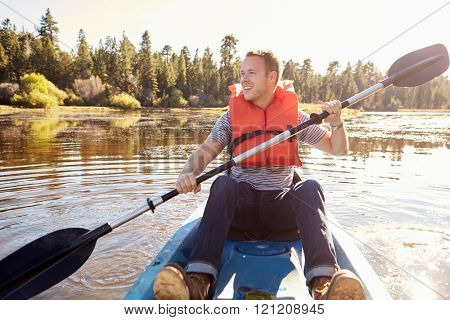 Man Wearing Life Preserver Rowing Kayak On Lake