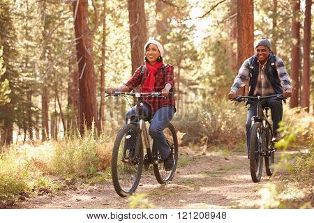Senior Couple Cycling Through Fall Woodland