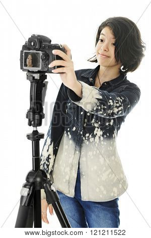 An attractive young teen shooting a selfie on a pro camera set up on a tripod.  On a white background.