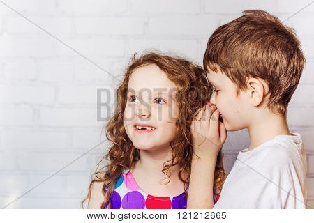 Little boy and his girl friend whispers in home.