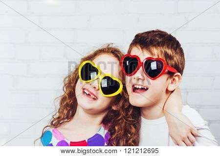 Embracing boy and girl with sunglassec heart shape. Happy toothless smiling friend.
