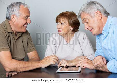 Senior Classmates Using Digital Tablet In Computer Class