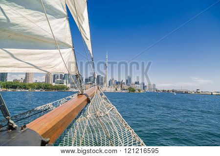 Gorgeous amazing beautiful view of a tall ship nose traveling on the lake toward Toronto downtown skyline on sunny summer day