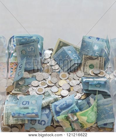 view of many various  bills and money coins on light grey background