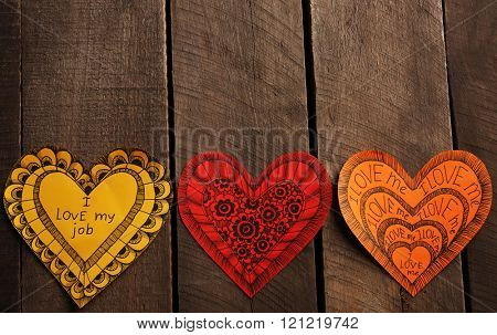 Varicolored Valentines with inscription on wooden background