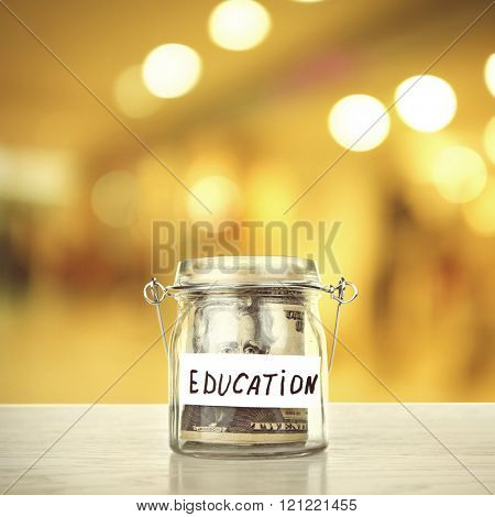 Jar for savings full of coins on bright background