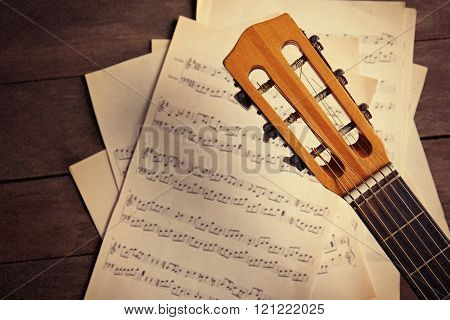 Music recording scene with guitar and musical notes on wooden background, closeup