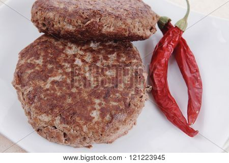fresh juicy beef meat hamburger with dry pepper on white plate over tablecloth with cutlery