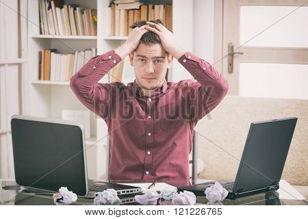 Overworked young man sitting at the desk and holding his head