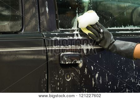 Closeup black rubber gloves working on washing car door window with soapy water
