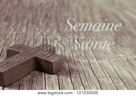 closeup of a small wooden cross on a rustic wooden surface, and the text semaine sainte, holy week in french, in sepia toning