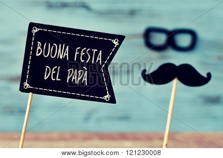 a black flag-shaped signboard with the text buona festa del papa, happy fathers day in italian, and a mustache and a pair of eyeglasses forming the face of a man, against a blue wooden background