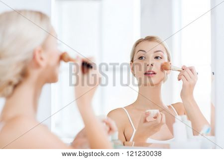 beauty, make up, cosmetics, morning and people concept - smiling young woman makeup brush and powder foundation looking to mirror at home bathroom