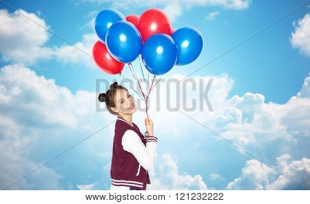 people, teens, holidays and party concept - happy smiling pretty teenage girl with helium balloons over blue sky and clouds background
