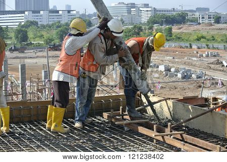 SELANGOR, MALAYSIA - MAY 2014: Construction workers are doing the concrete work using hose from the elephant crane or concrete pump crane on May 15, 2014 at Sepang, Malaysia.