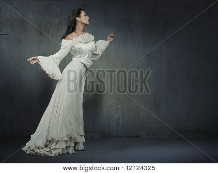 Beautiful woman wearing white dress over a grungy wall