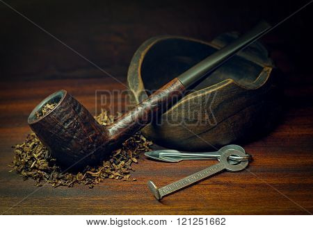 Smoking pipe and tobacco on old wooden background