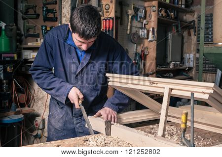 Carpenter Working On A Wooden Window Frame With A File