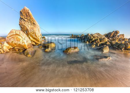 Smooth rockwaves bay inside large stone water straight up into sky below small stone reefs in long exposure to ocean waves lapping at the shore make the water cloudy beautifully smooth as when watching