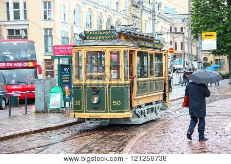 Helsinki, Finland - Jun 12 2014: Vintage sightseeing tourist tram in the city center and the pedestr