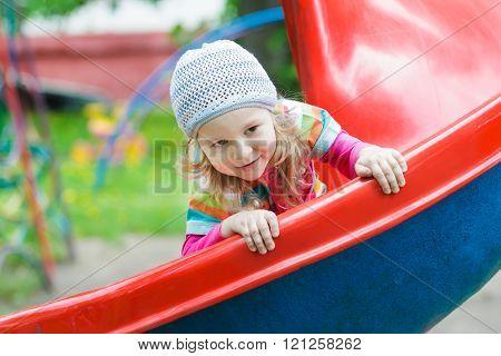 Smiling little blonde girl sliding down red plastic playground slide outdoors on spring