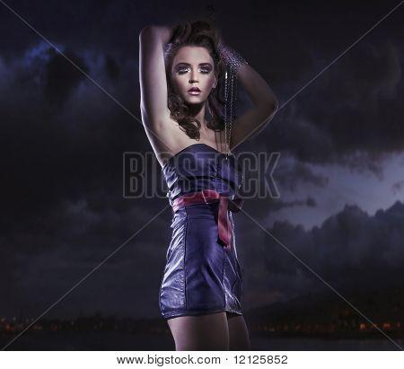 Joven belleza femenina sobre fondo de cielo nublado