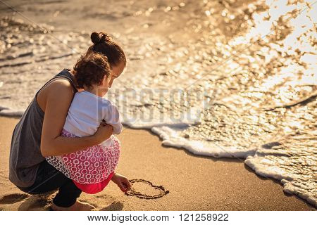 Mother and little daughter drawing heart on sand beach