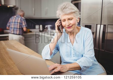 Senior woman talking on phone while using laptop and man working in kitchen at home